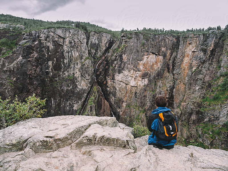 Backpacker Having a Rest While Looking at Voringfossen Waterfall by VICTOR TORRES for Stocksy United