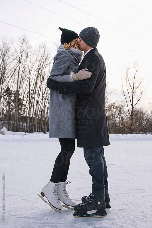 Young couple kissing on ice rink by Danil Nevsky for Stocksy United