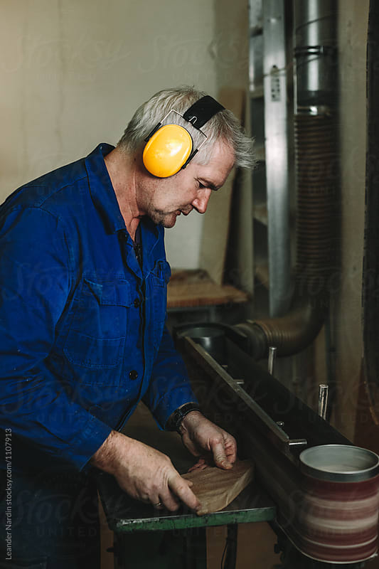 senior woodworker with yellow protection earmuffs working on a belt sander