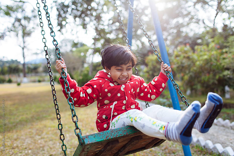 Cute Child enjoying the swing in a park by Saptak Ganguly for Stocksy United