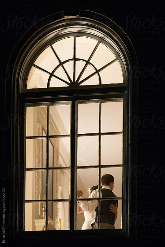 Bride and Groom Dance in a Large Picturesque Window by Brian McEntire for Stocksy United