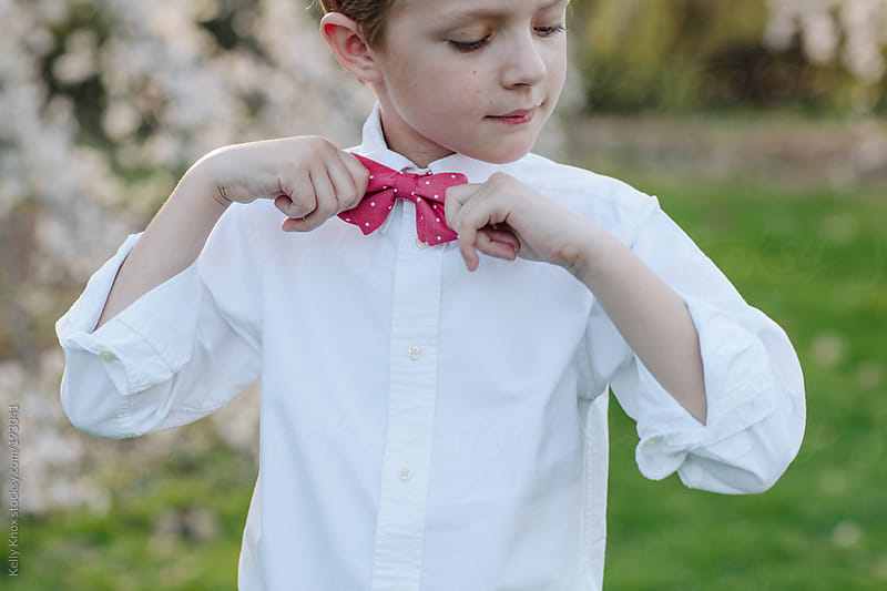 young boy adjusts his bow tie  by Kelly Knox for Stocksy United