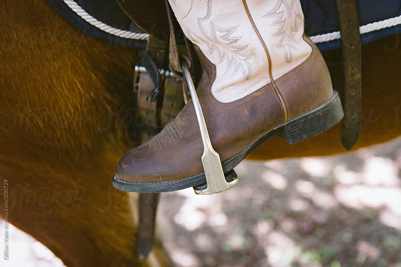 boot in stirrup by Gillian Vann for Stocksy United