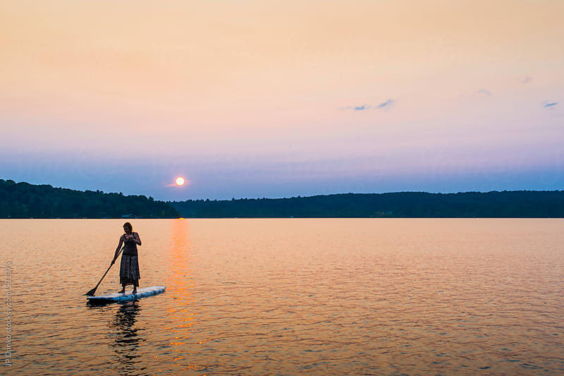 Silhouette of Woman In Dress On Stand Up Paddle Board At Sunset by JP Danko for Stocksy United