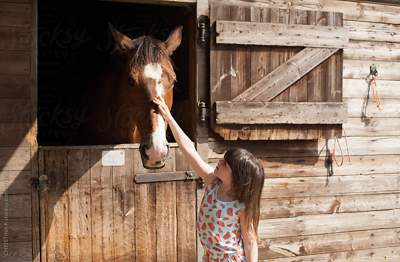 Little girl stroking a horse in a stable by CHRISTINA K for Stocksy United