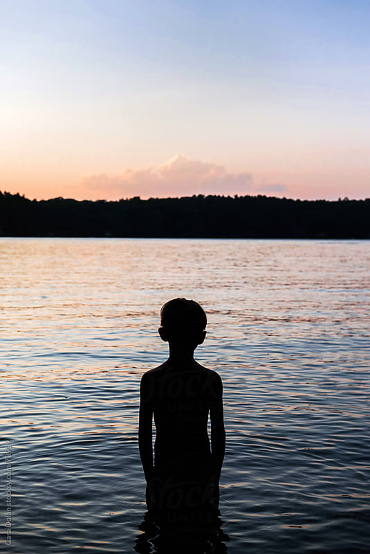 Boy in silhouette stands looking out over lake water at dusk by Cara Dolan for Stocksy United
