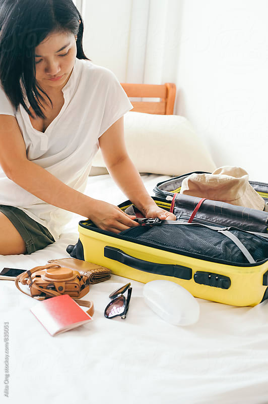 Woman packing a suitcase for a trip by Alita Ong for Stocksy United