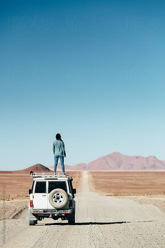Woman on a roadtrip in an expansive empty desert by Micky Wiswedel for Stocksy United