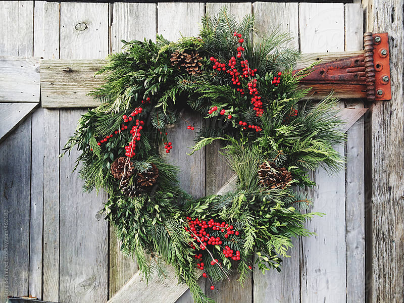 Happy Holiday Merry Christmas wreath with greens and berries by Greg Schmigel for Stocksy United