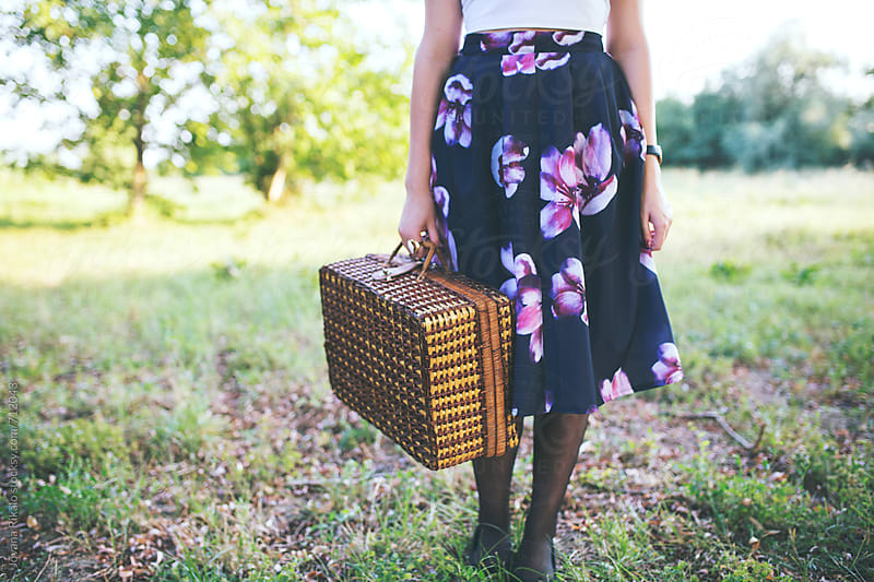 Young woman in floral dress holding a picnic basket by Jovana Rikalo for Stocksy United