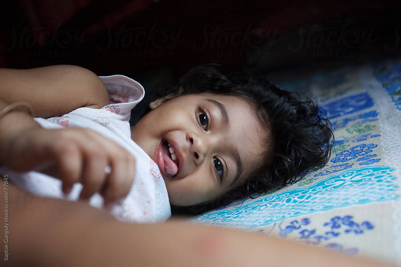 Cute little girl sticking out tongue while lying on bed by Saptak Ganguly for Stocksy United