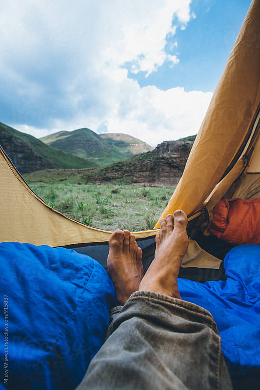 point of view looking out of a camp tent with mans feet in the foreground by Micky Wiswedel for Stocksy United