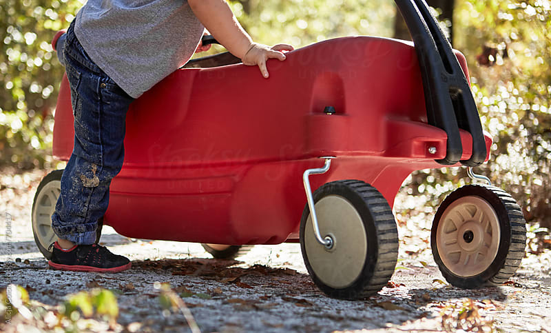Toddler boy entering a red wagon by Alicja Colon for Stocksy United
