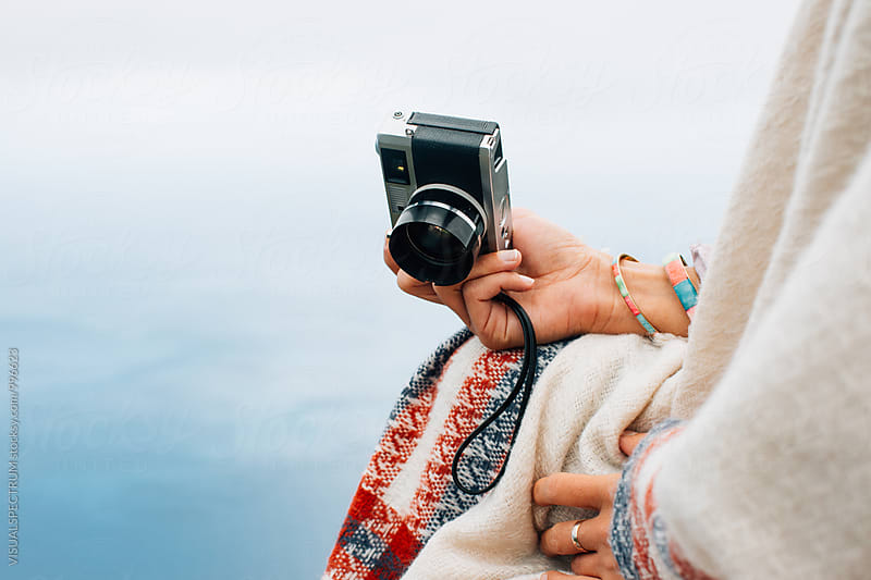 Closeup of Woman Sitting on Island Viewpoint and Holding Old-Fashioned Rangefinder Camera by Julien L. Balmer for Stocksy United