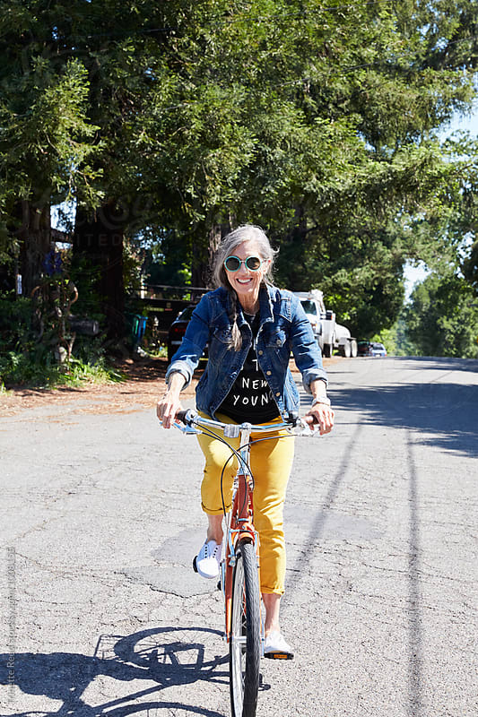 Portrait of stylish senior woman riding a bike by Trinette Reed for Stocksy United
