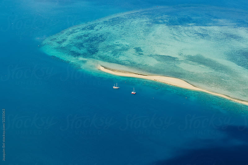 Boats moored next to a reef by Joaquim Bel for Stocksy United