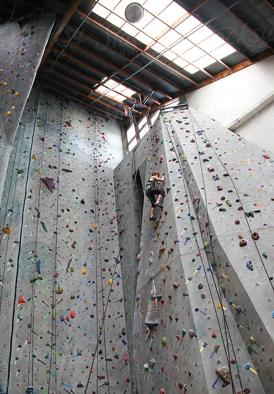 Young girl climbing to the top of the rock wall by Carolyn Lagattuta for Stocksy United