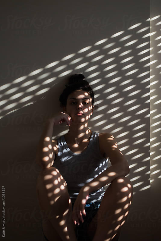 Portrait of beautiful woman with light on her skin by Kate & Mary for Stocksy United