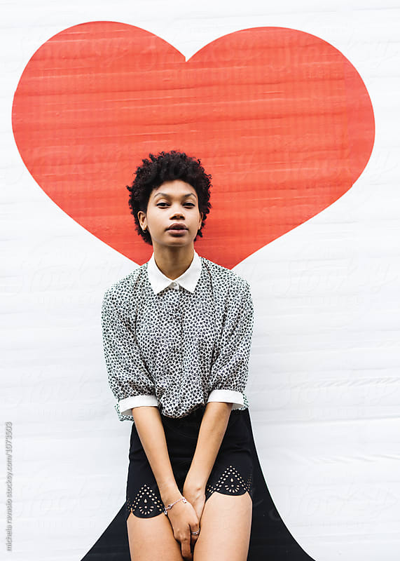 Attractive afro woman leaning against a wall with a red heart drawn by michela ravasio for Stocksy United