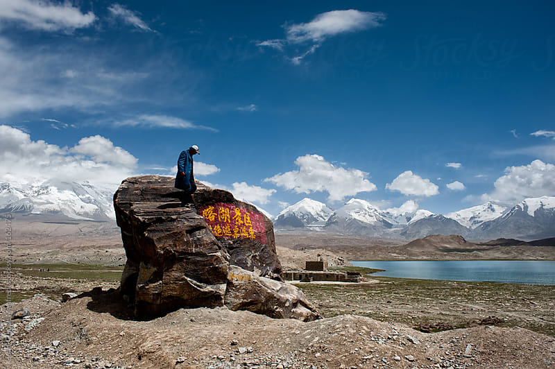 nomad man gets out of his his rock in a wasteland, in the background the Himalaya's mountains by Jean-Claude Manfredi for Stocksy United
