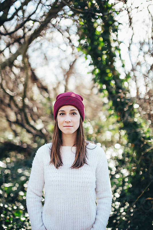 Content young caucasian woman staring at camera outside wearing sweater and toque by Rob and Julia Campbell for Stocksy United