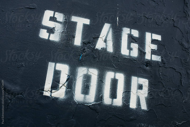 The words STAGE DOOR painted on wall by Paul Edmondson for Stocksy United