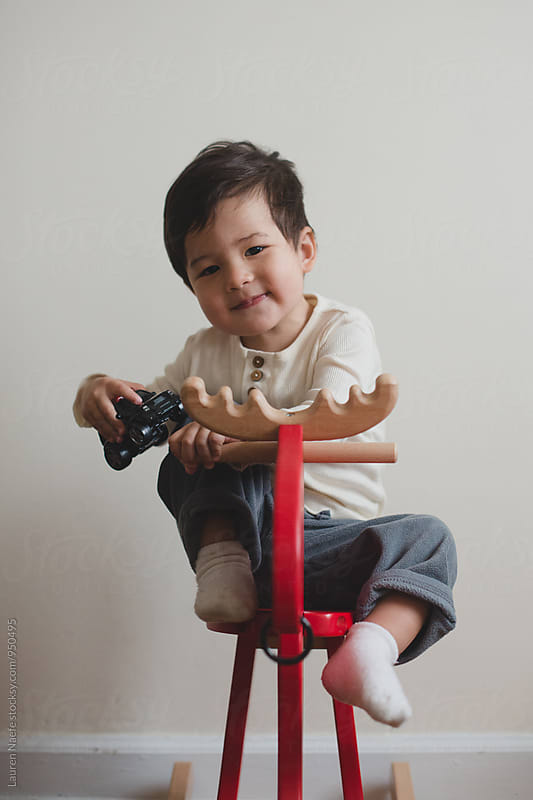 Little kid on rocking horse by Lauren Naefe for Stocksy United