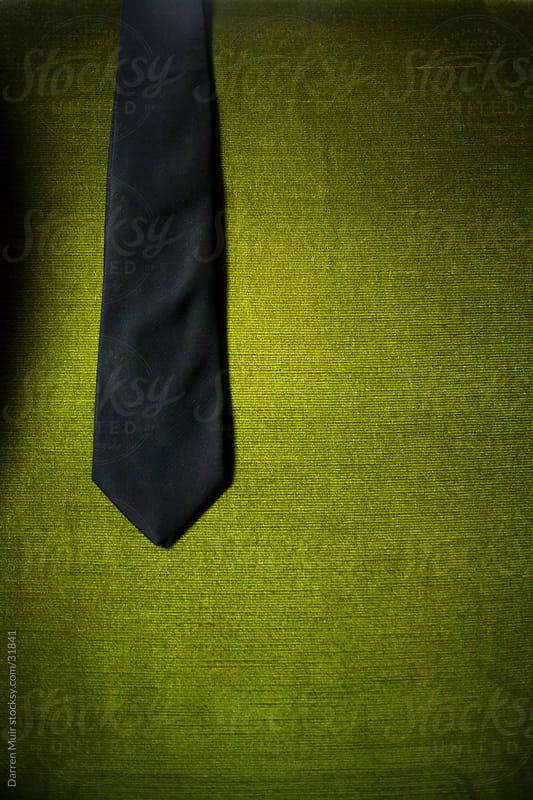 Black tie draped over a green velvet chair. by Darren Muir for Stocksy United