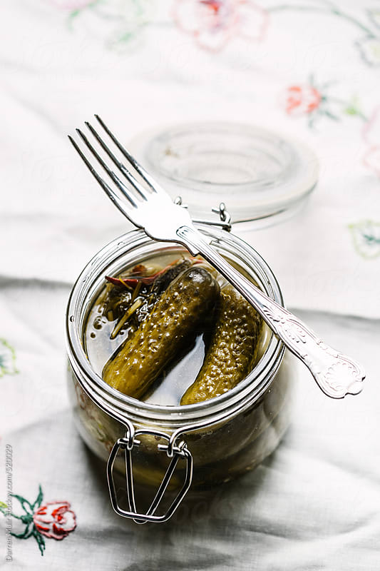 Pickles in open glass jar. by Darren Muir for Stocksy United