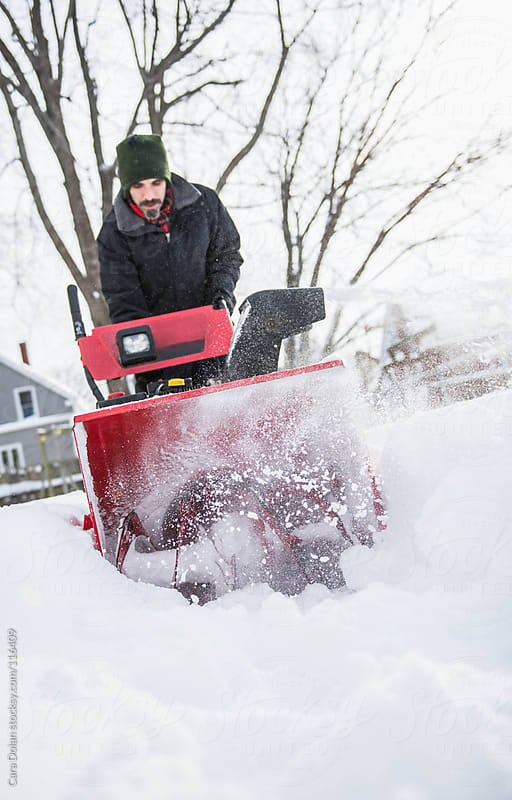 Man uses a snow blower to clear the snow away from his house by Cara Dolan for Stocksy United
