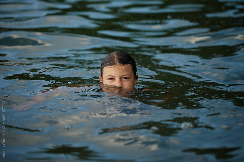 Girl peeking out of water by Amanda Worrall for Stocksy United