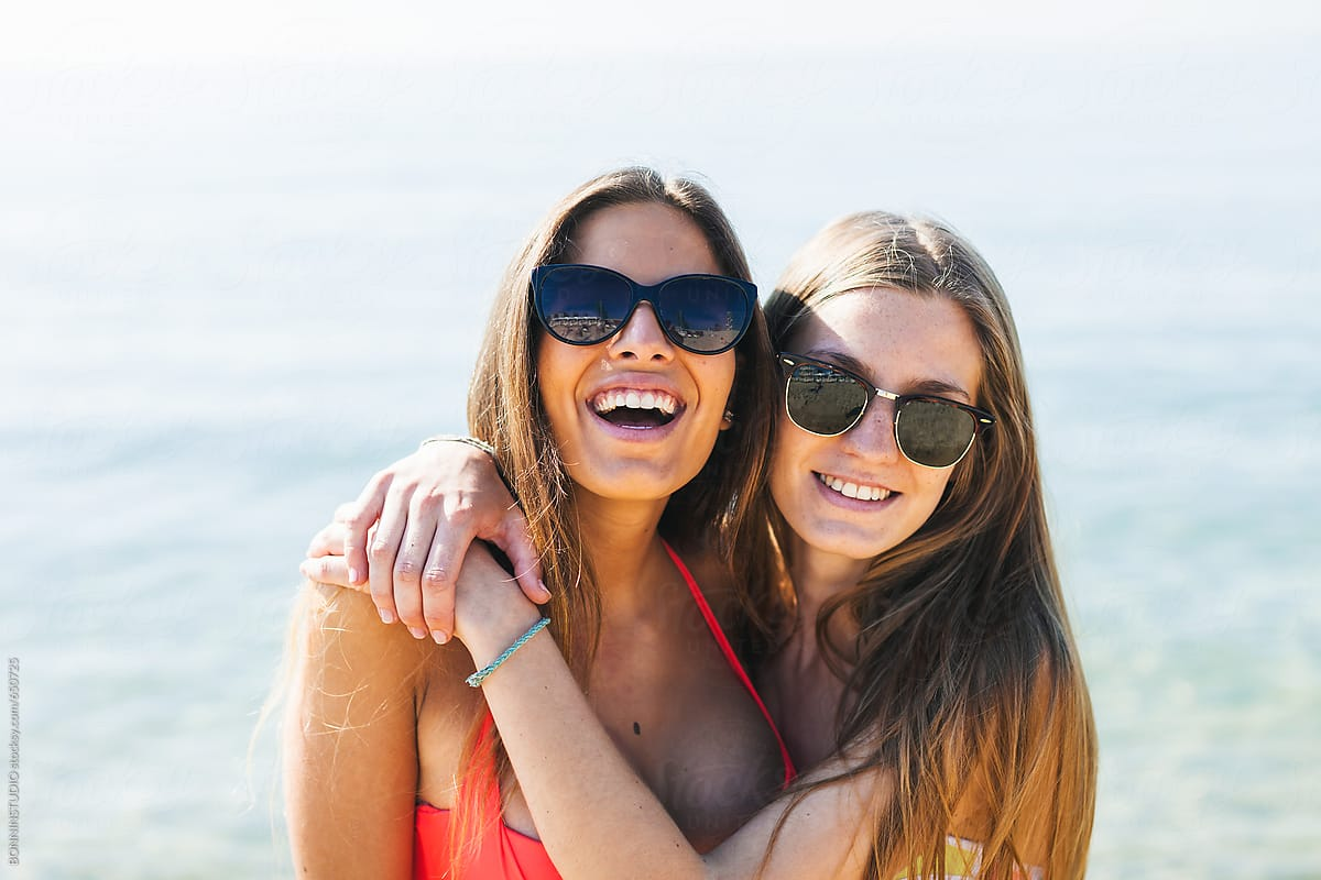 27a836829f Portrait of young women wearing sunglasses standing on the beach. by  BONNINSTUDIO for Stocksy United