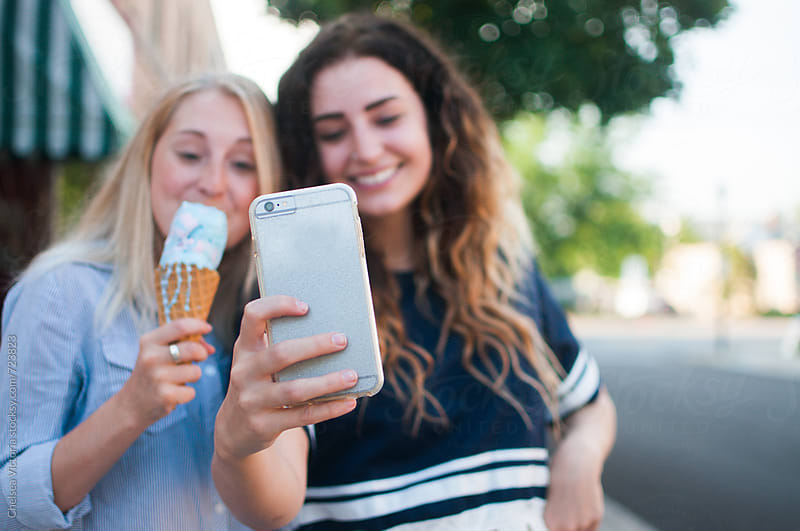 Best friends sharing ice cream and taking a picture by Chelsea Victoria for Stocksy United