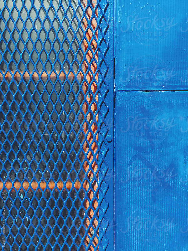 Protective metal screen covering window on building wall, close up by Paul Edmondson for Stocksy United