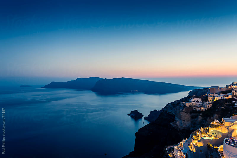 Sunset over Oia in Santorini looking towards Thirassia by Paul Phillips for Stocksy United