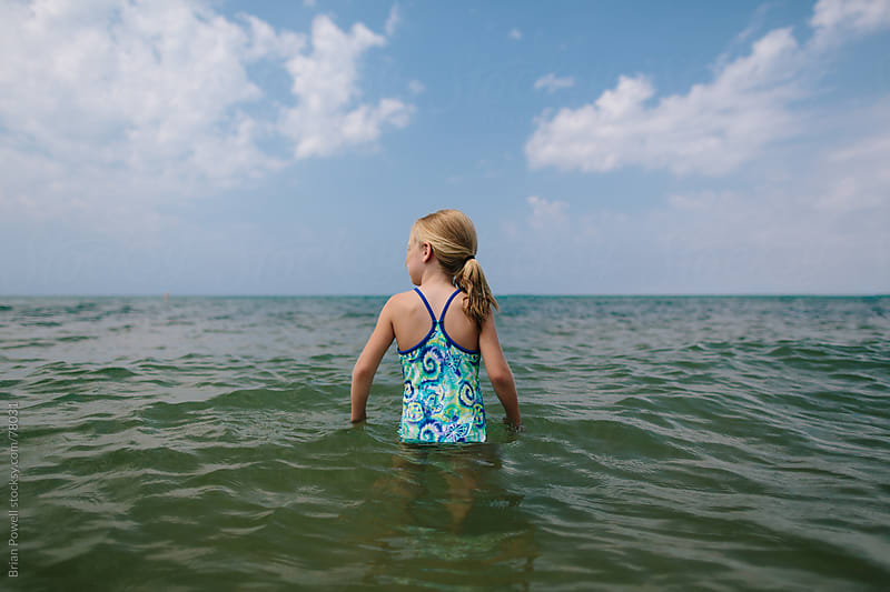 girl ventures out into endless water by Brian Powell for Stocksy United