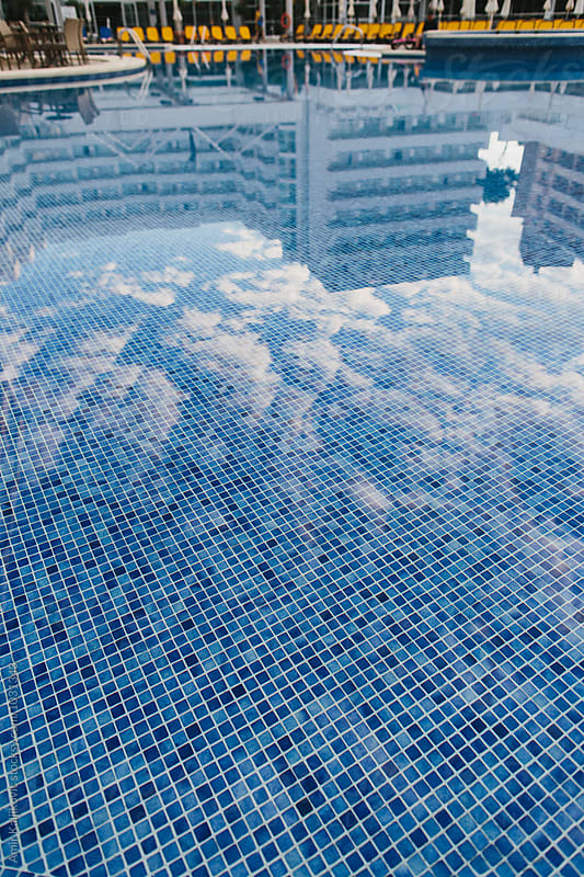 Modern resort hotel reflected in a swimming pool by Amir Kaljikovic for Stocksy United