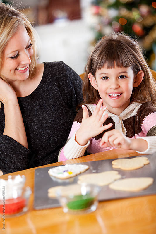 Gingerbread: Girl Having Fun with Mother at Christmas by Sean Locke for Stocksy United