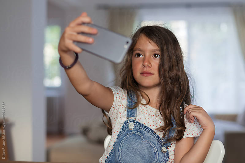 Child taking selfie at home. by Dejan Ristovski for Stocksy United