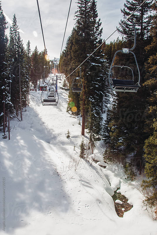 Riding a chair lift through snowy trees in winter by Angela Lumsden for Stocksy United