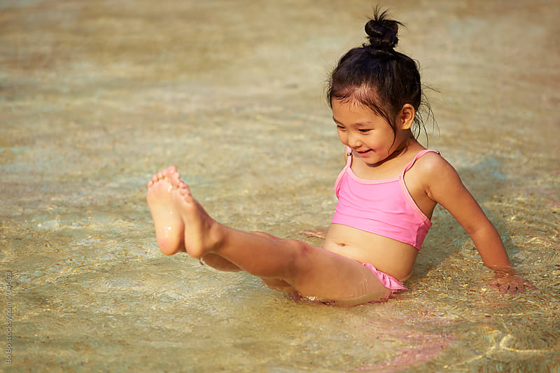 one happy little asian girl enjoy summertime in swimming pool by Bo Bo for Stocksy United