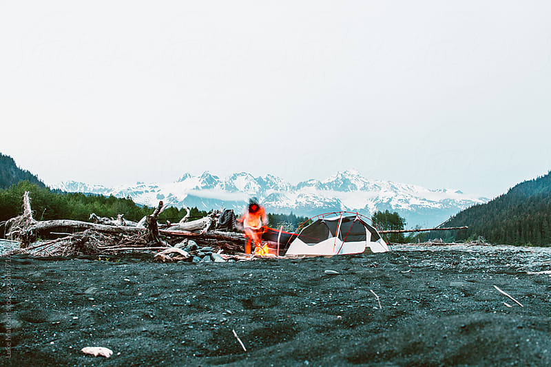 Man Tends To A Campfire At A Makeshift Campsite In The Alaskan Wilderness by Luke Mattson for Stocksy United