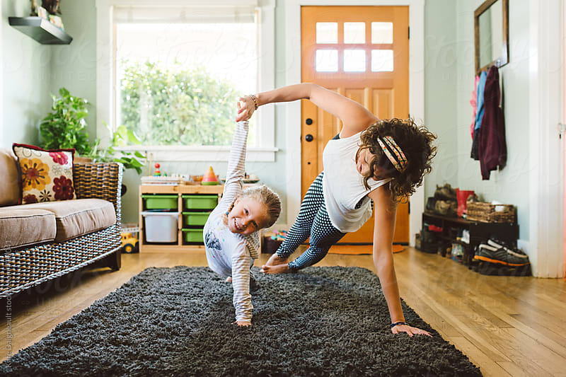 Young girl does yoga in living room with her mom. by Kate Daigneault for Stocksy United