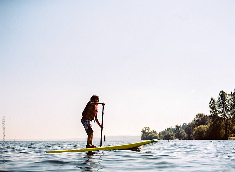 Boy paddle boarding by Heather Perera for Stocksy United