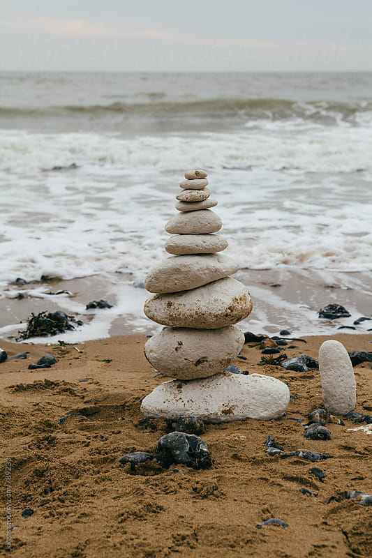 Stack of white chalk zen stones on a beach with approaching waves by kkgas for Stocksy United
