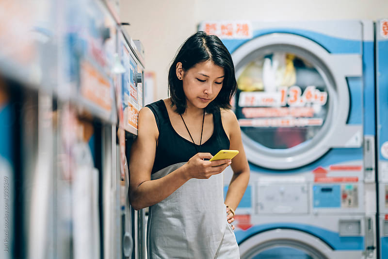 Young Asian woman waiting in a laundromat by Juri Pozzi for Stocksy United