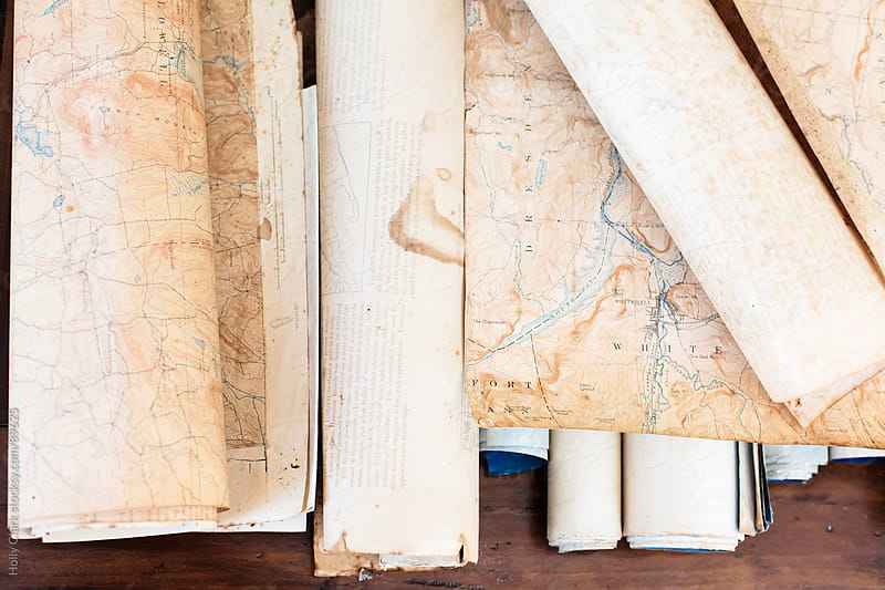 Pieces of an antique map and scrolls sit on a wooden table. by Holly Clark for Stocksy United