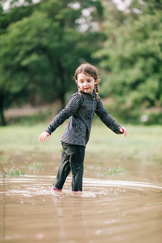 Preschool age Girl in a Brown Puddle by Gary Radler Photography for Stocksy United