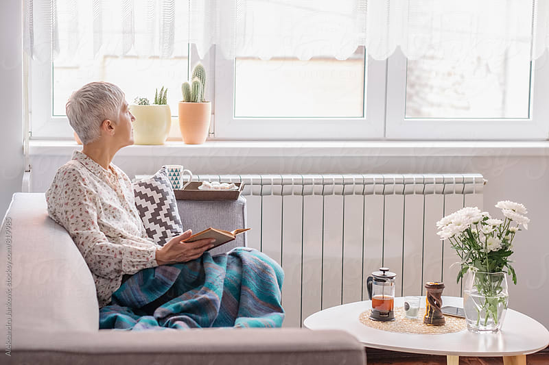 Senior Woman Reading a Book and Looking Out the Window by Aleksandra Jankovic for Stocksy United