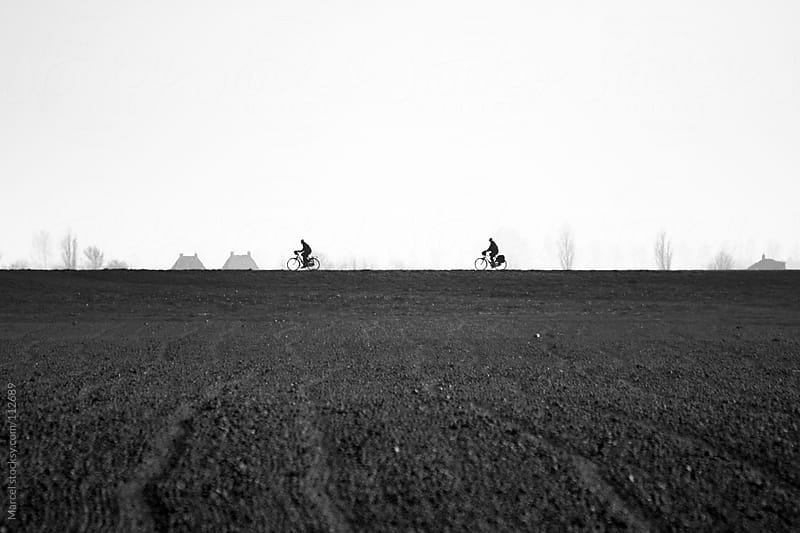 Two cyclists on a small dike in Holland by Marcel for Stocksy United